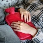 Woman with a hot water bottle on checked pyjamas to indicate pain relief