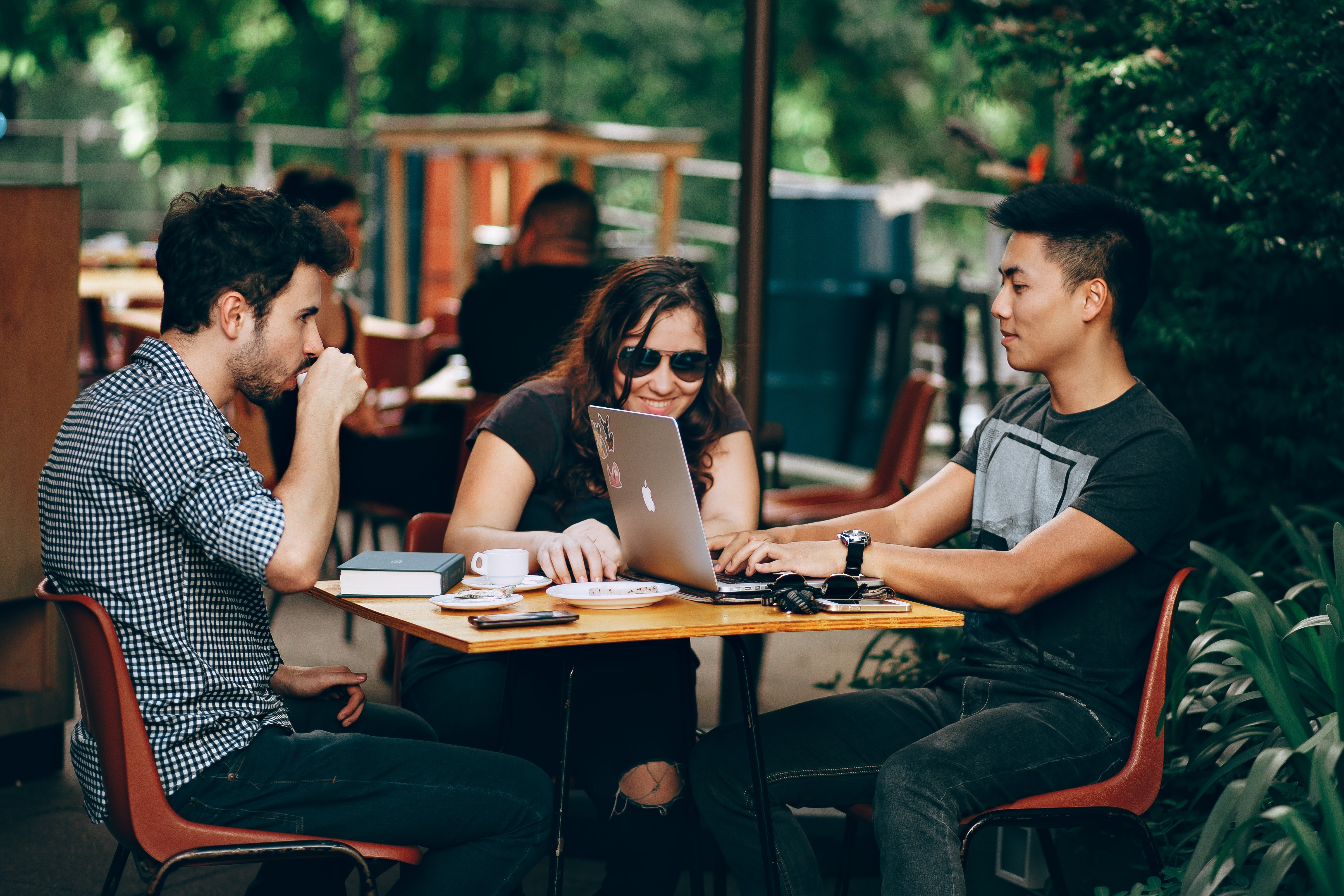 Three people sitting at a table to illustrate work-life balance