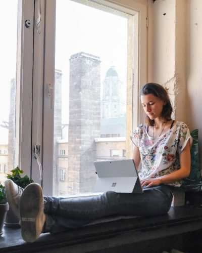 Woman on window set writing- 6 self-care tips for freelance writers