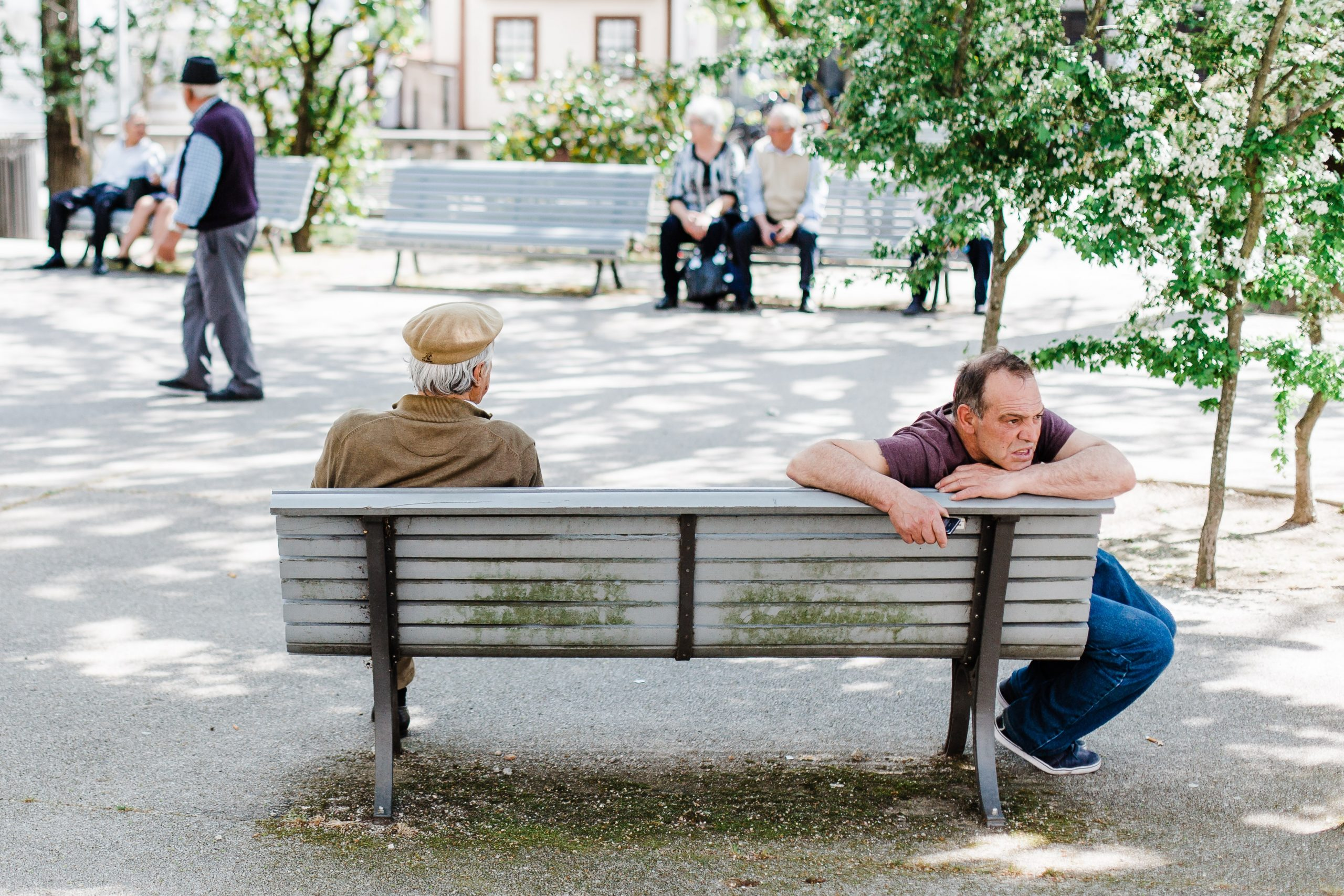 Two elderly men sit on a bench in Portugal not speaking and isolated from the other side of the park