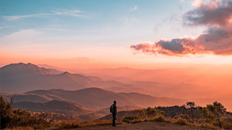 Man Standing on a hill in Thailand with a blue and pink sunrise by Colton Duke