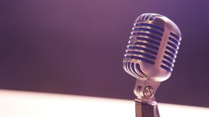 Podcasting mic on a purple and white background