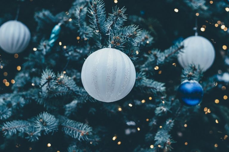 A frosted white bauble on a deep green tree with a few lights