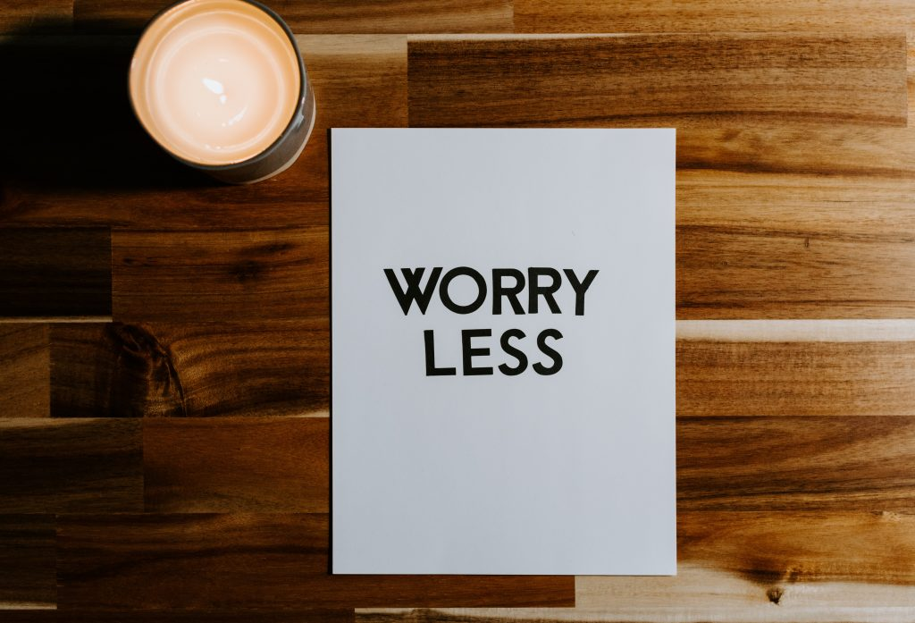 A white piece of paper with the words Worry Less in black bold font on a wooden table with a light W