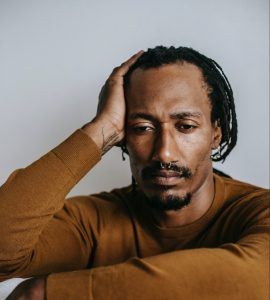 A Black man with braids and a mustard jumper sits on the floor with his knees up looking pensive . How to handle stressful thoughts.