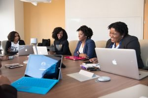 Marcia Ore: 4 women around a table with laptops talking