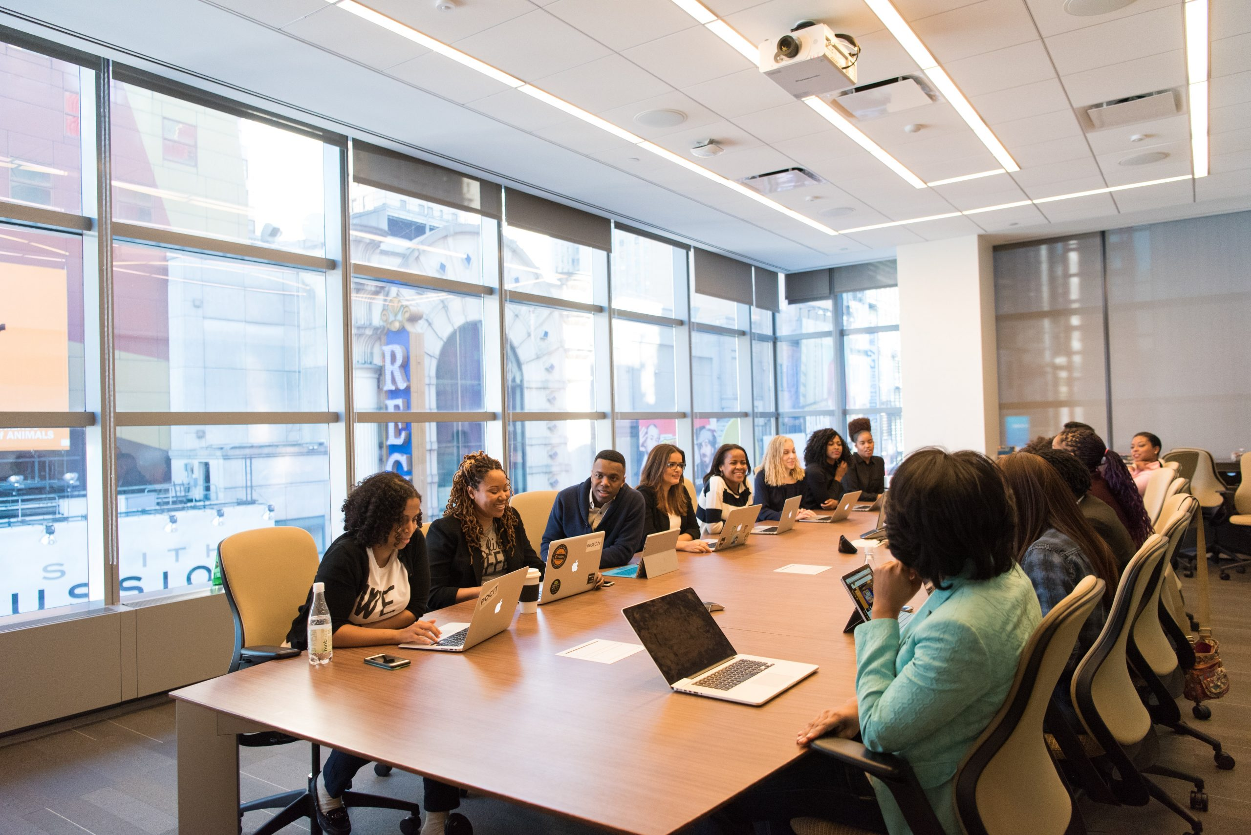 Diverse Minds Associate: Photo of a board meeting with a variety of people
