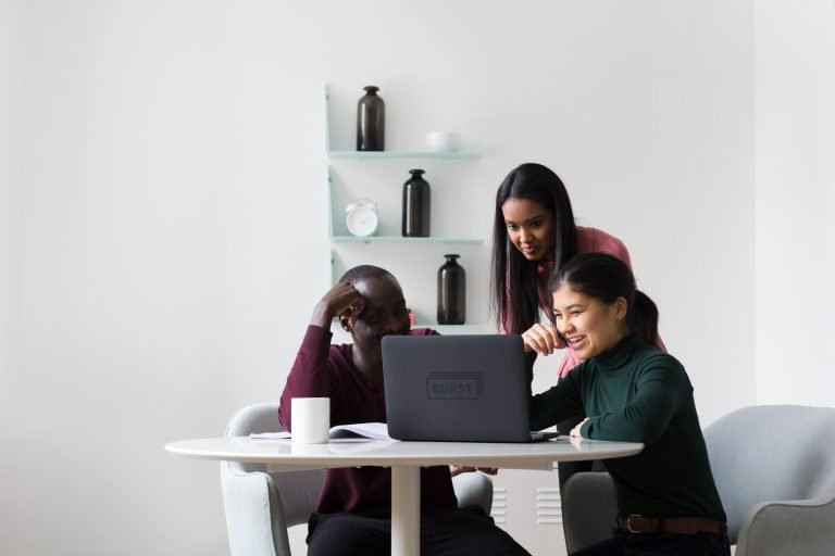Introducing Soma Ghosh :Three people looking at a laptop on a small circular white table.